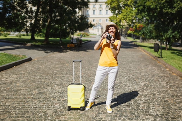 Traveler tourist woman in yellow casual clothes hat with suitcase taking pictures on retro vintage photo camera outdoor. girl traveling abroad to travel on weekend getaway. tourism journey lifestyle.