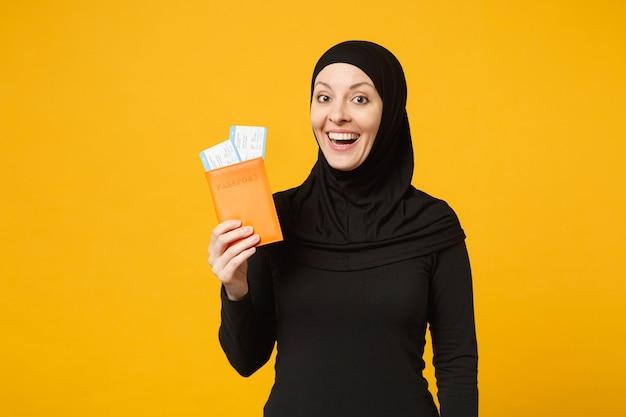 여행자 관광 hijab 검은 옷에 젊은 아라비아 무슬림 여성은 노란색 벽 초상화에 고립 된 여권 티켓을 잡아. 사람들이 종교적인 라이프 스타일 개념.