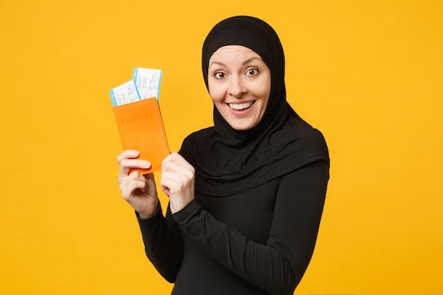 Путешественник туристическая молодая арабская мусульманская женщина в черной одежде хиджаба держит паспортные билеты, изолированные на портрете на желтой стене. концепция религиозного образа жизни людей.