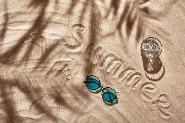 Аксессуары для отдыха путешественников разложены на белом песчаном пляже, вид сверху