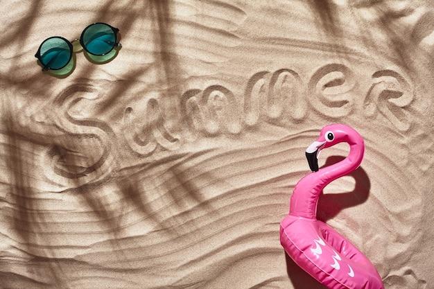 여행자 휴가 액세서리는 하얀 해변 모래 평지 위에 놓여 있습니다.