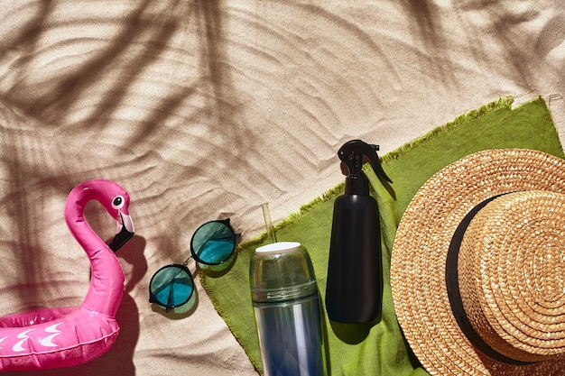 Traveler vacation accessories are laid out on a white beach sand flat lay top view