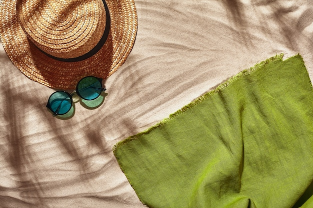Traveler vacation accessories are laid out on a white beach sand. flat lay, top view.