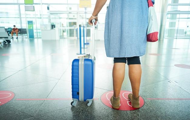 사회적 거리를 유지하는 공항에서 기다리는 여행자. covid 19를 피하기위한 사회적 거리.