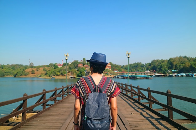Traveler walking on the mon bridge, the longest handmade wooden bridge in thailand, sangkhlaburi district, kanchanaburi province, thailand