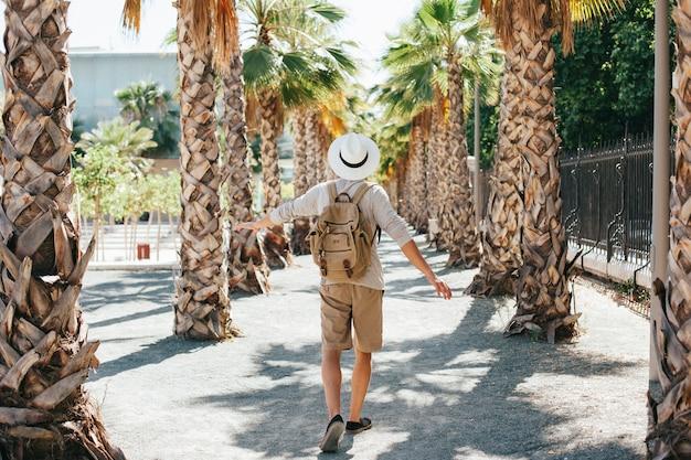 Traveler walking through palm trees