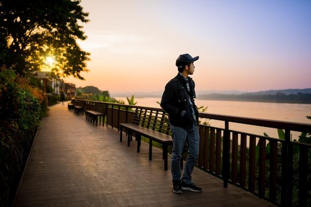 Traveler walking over wooden bridge near the river in sunset