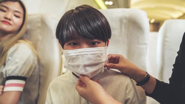 民間航空機で旅行中にフェイスマスクを着用している旅行者。