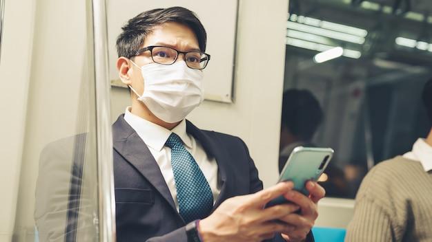 公共電車で携帯電話を使用しながらフェイスマスクを着用している旅行者。ラッシュアワー通勤の概念におけるコロナウイルス病またはcovid19パンデミックの発生と都市のライフスタイルの問題。