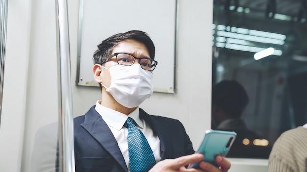 대중 열차에서 휴대 전화를 사용하는 동안 얼굴 마스크를 쓴 여행자