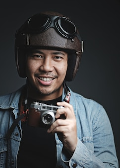 Traveler wearing retro helmet and holding vintage camera