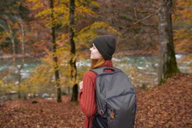 秋の森の落ち葉の木川モデルでバックパックと灰色の帽子をかぶった旅行者