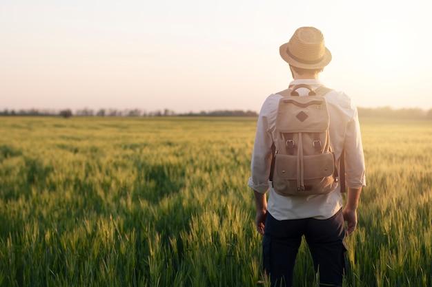 小麦の夜明けの分野でバックパックを持つ旅行者は太陽に手を上げます