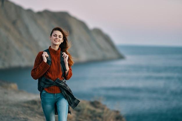 海の近くの自然の山でバックパックを持って旅行者