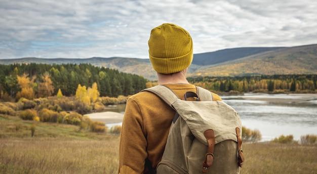 배낭을 메고 숲을 따라 빈 길을 걷고 있습니다. 자유, 여행, 하이킹 및 가을 분위기의 개념