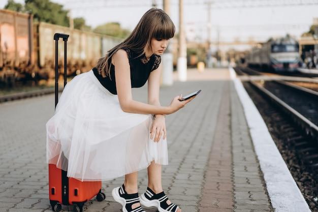Путешественник с красным чемоданом в белой юбке ждет поезд на вокзале