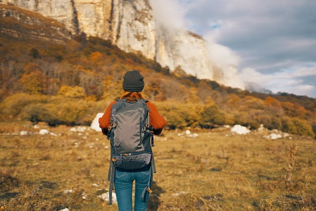 A traveler with a backpack in a denim hat are walking on the nature mountains