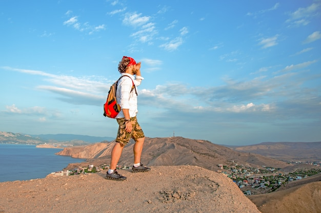 Traveler with a backpack on his back is standing on the top of a mountain, admiring the scenery