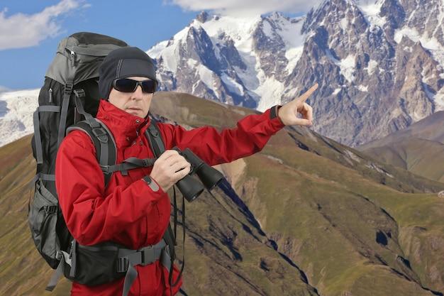 손가락으로 멀리 떨어진 마운트 지점의 경사면에 쌍안경을 들고 배낭 빨간색 재킷을 입은 여행자