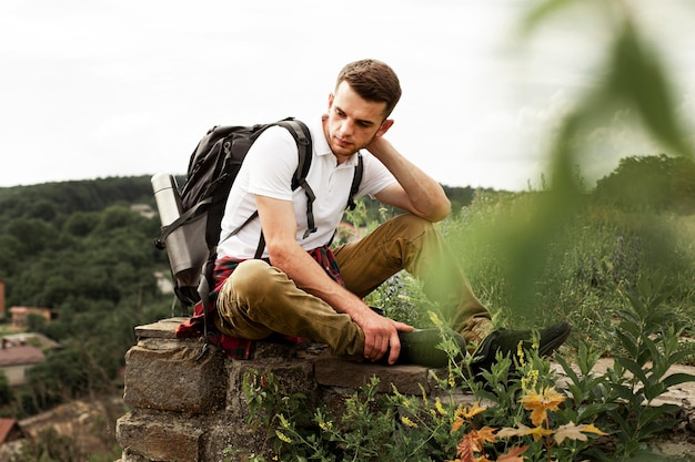 Traveler with backpack resting on rock