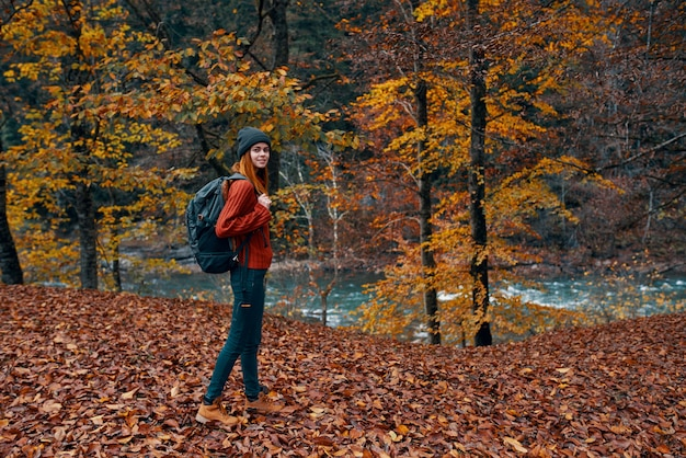 A traveler with a backpack walks in the park in nature near the river in autumn