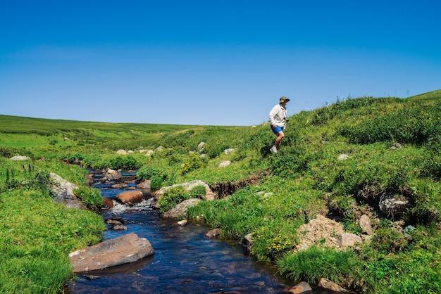 マウンテンクリークの近くにカメラを持った旅行者。観光客の冒険。山でのハイキング。高地の豊かな植生。