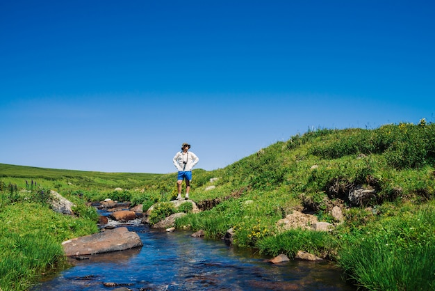 Traveler with camera on stone in mountain creek. adventure of tourist. hiking in mountains. rich vegetation of highlands. stream of clear water in brook. vivid sunny landscape of majestic nature.