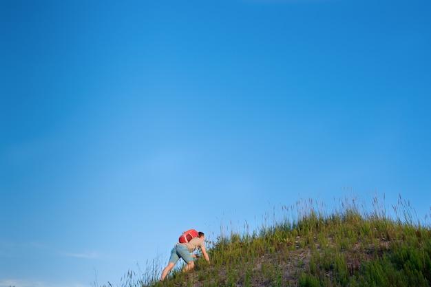 Путешественник с оранжевым рюкзаком, гуляющий по холмам на фоне голубого неба