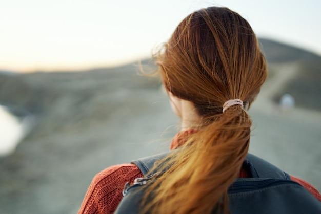 後ろの山の風景空の背面図に赤い髪とバックパックを持つ旅行者