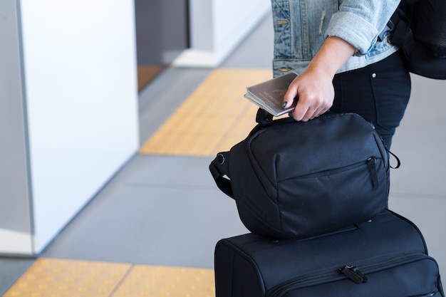 Traveler with suitcase waiting for train in platform