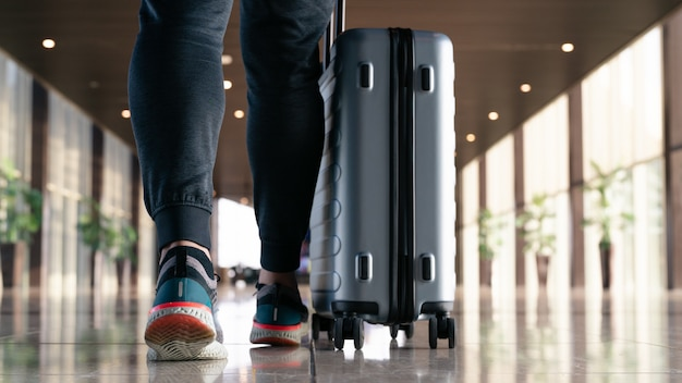 Traveler with suitcase walking with carrying luggage and passenger for tour in the airport terminal for air traveling