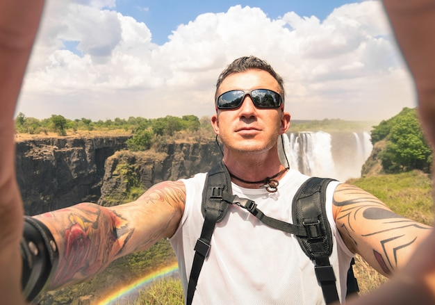 Traveler with tattoos taking selfie at victoria falls
