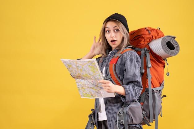 Donna viaggiatrice in confusione con lo zaino che tiene mappa