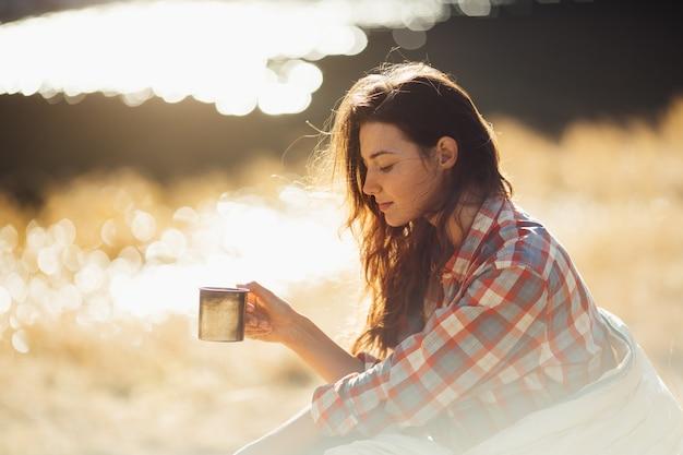 호수 근처에서 커피 한잔과 함께 산에서 하이킹을 하는 여행자 여성