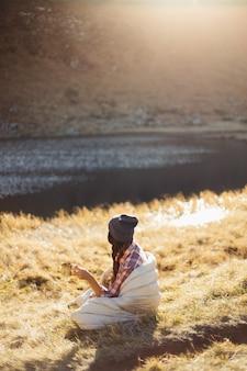 湖の近くでコーヒーを飲みながら山でハイキングする旅行者の女性