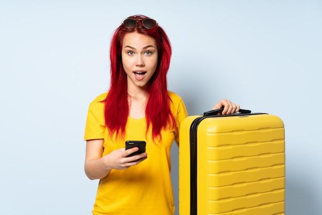 驚いて、メッセージを送信する青い壁に分離されたスーツケースを持った旅行者女性
