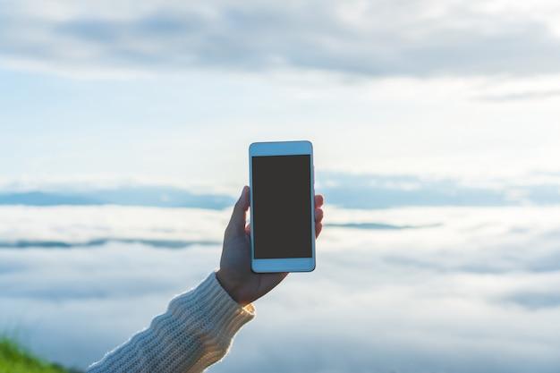 霧の層状の山の風景と朝の美しい空と空きスペースのための携帯電話の空白の画面を保持している旅行者の女性。
