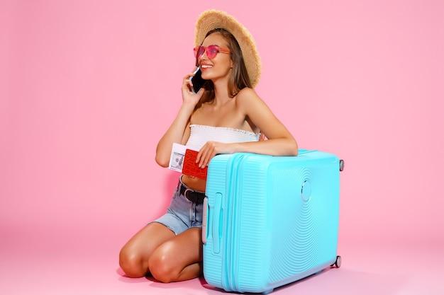 Женщина-путешественница держит деньги на паспортные билеты с чемоданом и вызывает такси в концепцию путешествия в аэропорт