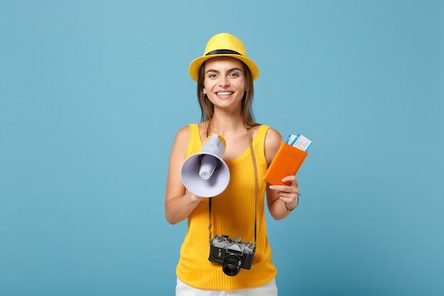 青のチケットメガホンカメラを保持している黄色のカジュアルな服と帽子の旅行者の女性
