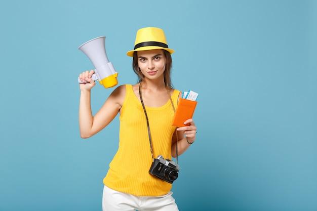 노란색 캐주얼 옷과 파란색 티켓 확성기 카메라를 들고 모자에 여행자 여자