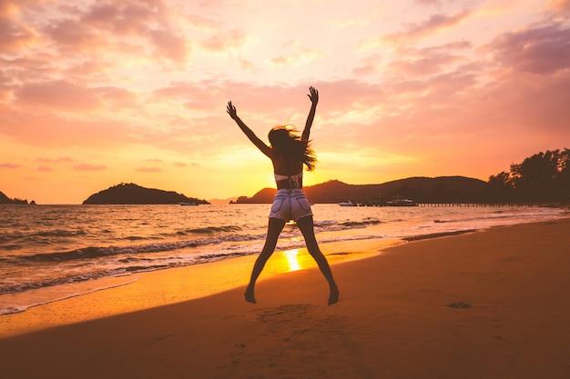 Traveler woman jumping on beach at sunset