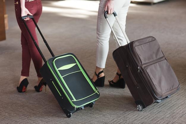 スーツケースを持って歩く旅行者の女性の足