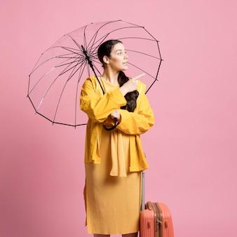 Traveler woman looking away while holding an umbrella