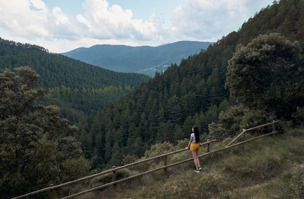 Traveler woman looking at the mountains and the forest. travel and active lifestyle concept