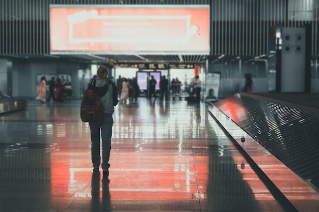旅行者の女性の計画とバックパック、女の子の観光客はバッグを保持し、ホールの飛行機の出発で荷物の近くで待っています。旅行のコンセプト。到着ホール。観光客は空港内の出口に行きます