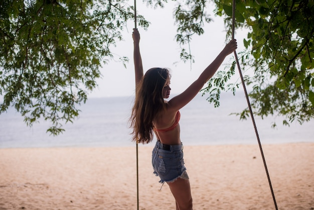Traveler woman relaxing on wooden swing at the beach