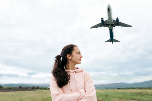 Traveler woman stands and looks the airplane taking off