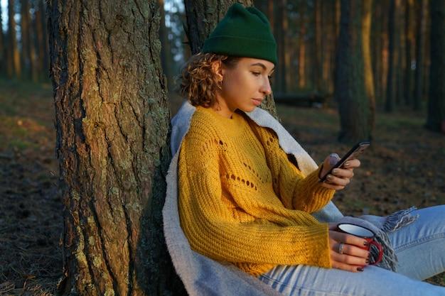Женщина-путешественница, отправляющая текстовые сообщения, чтение или электронную почту в смартфоне, расслабленно сидит с чашкой чая под деревом