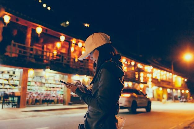 Traveler woman using mobile phone in street market