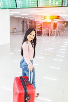 Traveler woman walking carrying a suitcase in international airport